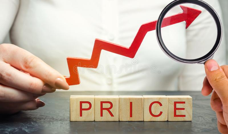 A woman holds a red up arrow above the wooden blocks and the inscription Price. Growing market value. Pricing. Market economy. Inflation. Consumer price index stock image