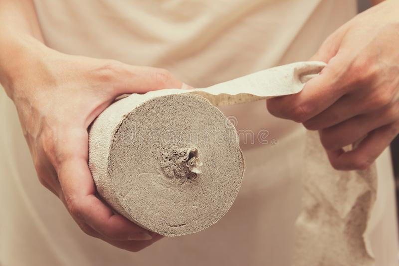 Woman holding toilet paper. A woman holds a roll of toilet paper and is going to tear off part of it stock photos