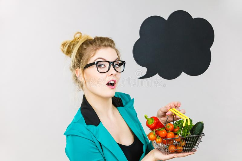 Woman holds shopping cart with vegetables, copy space stock photo