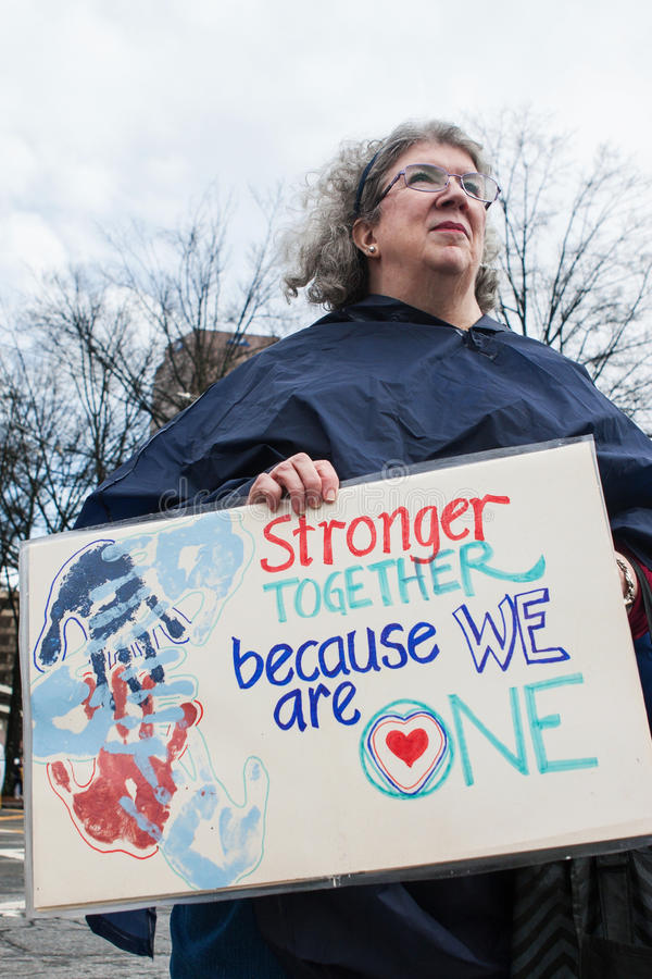 Woman Holds Sign At Atlanta Social Justice March. Atlanta, GA, USA - January 21, 2017: A woman holds a sign that says `Stronger together because we are one` as stock photo