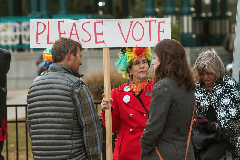 Woman Holds Sign Urging People To Vote At Halloween Parade royalty free stock photos