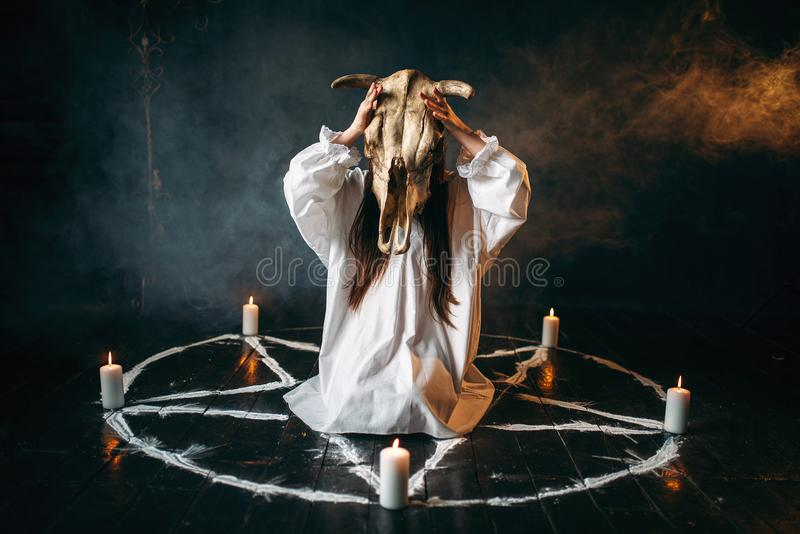 Woman holds skull of the animal in hand, occultism. Young woman in white shirt holds skull of the animal in hands, pentagram circle with candles, smoke all stock photos
