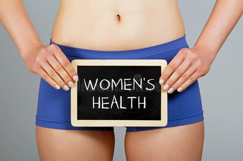 Woman holds a small chalkboard with `Women`s health` inscription stock images