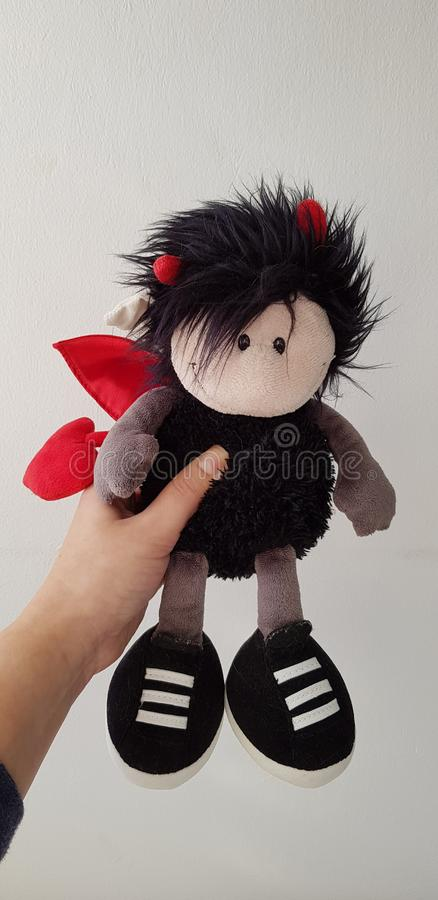 Woman holds a soft devil toy stock photography