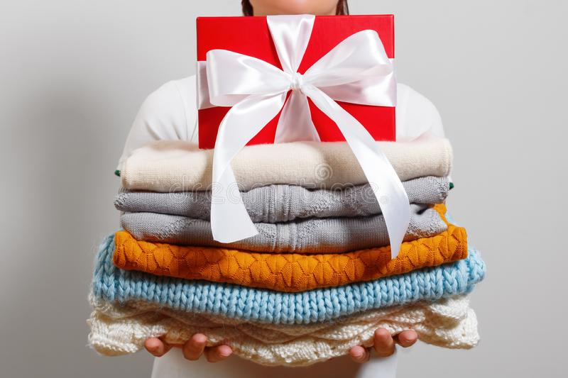 A woman holds a stack of warm knitted sweaters and a box with a gift on a gray wall background. A woman holds a stack of warm knitted sweaters and a box with a royalty free stock photos