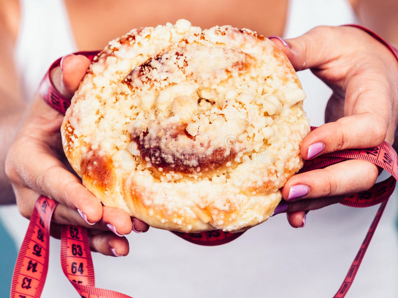 Woman holds sweet bun recommending non sugar diet. Unhealthy nutrition overweight concept. Fit female saying no to sweet dessert. Woman dietician holding sweet stock photo
