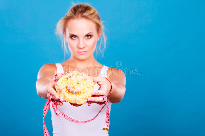 Woman holds sweet bun recommending non sugar diet. Unhealthy nutrition overweight concept. Fit female saying no to sweet dessert. Woman dietician holding sweet royalty free stock photo