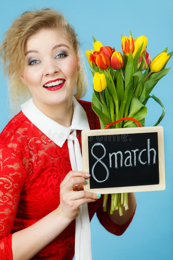Woman holds tulips, board with text 8 march stock image