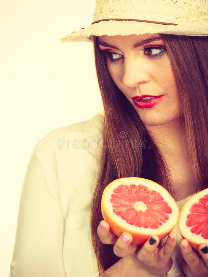 Woman holds two halfs of grapefruit citrus fruit in hands stock photo