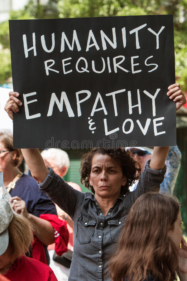 Woman Holds Up Sign About Humanity At Anti Gun Rally. Atlanta, GA, USA - April 29, 2017: A woman holds a sign saying `Humanity requires empathy and love` at a stock images