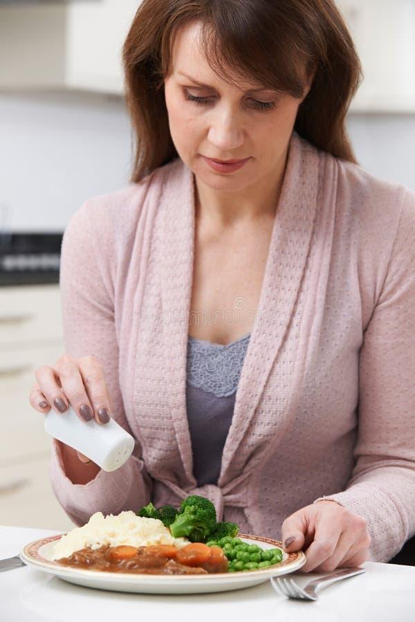 Woman At Home Adding Salt To Meal. Woman At Home At Table Adding Salt To Meal royalty free stock photos