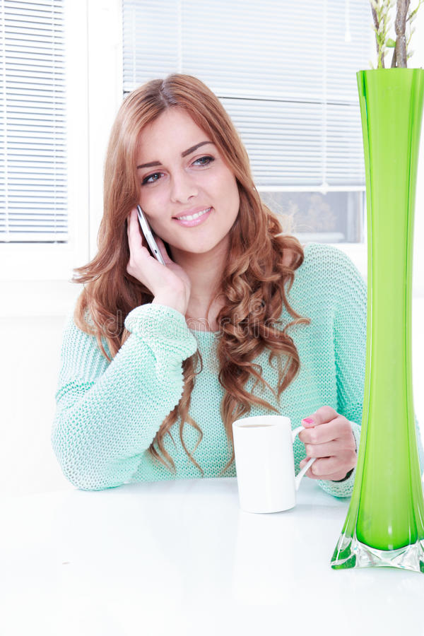 Woman at home drinking coffee and talking on mobile phone. Woman at home drinking coffee and talking sitting at the table with vase with flowers in front stock photography