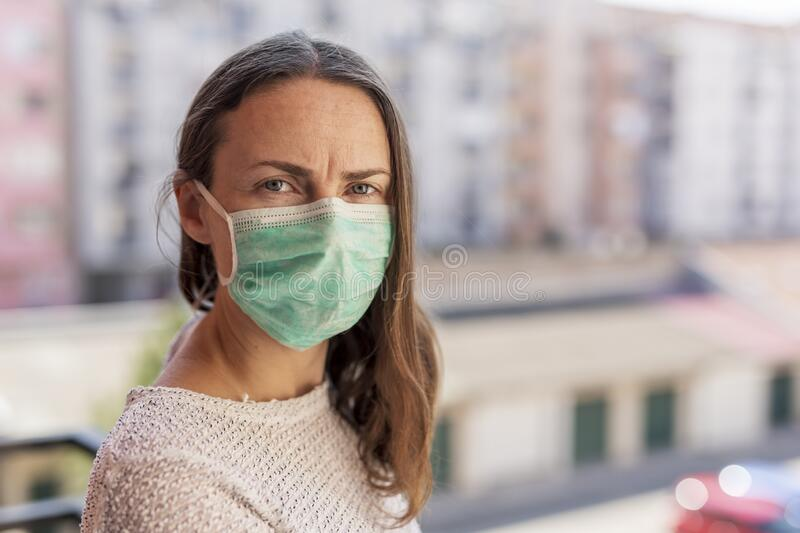 Woman in home isolation during coronavirus lockdown. Woman in home isolation on a balcony, wearing medical face protection mask as part of coronavirus protection royalty free stock photo