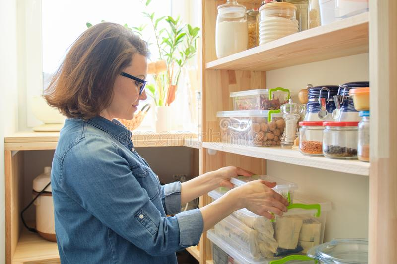 Woman at home in kitchen, near wooden shelves with food stock photo