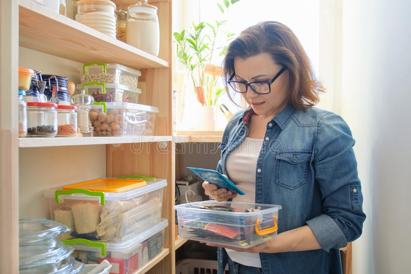 Woman at home in kitchen, near wooden shelves with food royalty free stock image
