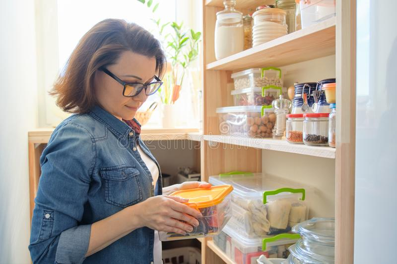 Woman at home in kitchen, near wooden shelves with food stock image