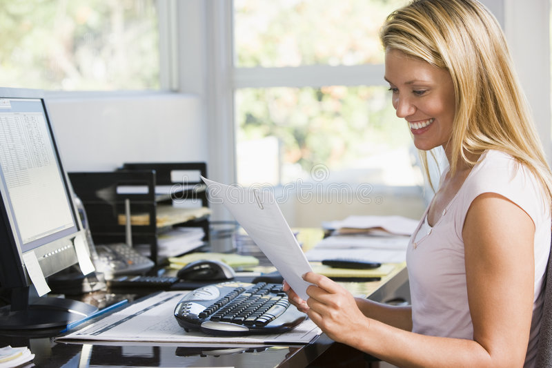 Woman in home office with computer and paperwork royalty free stock images