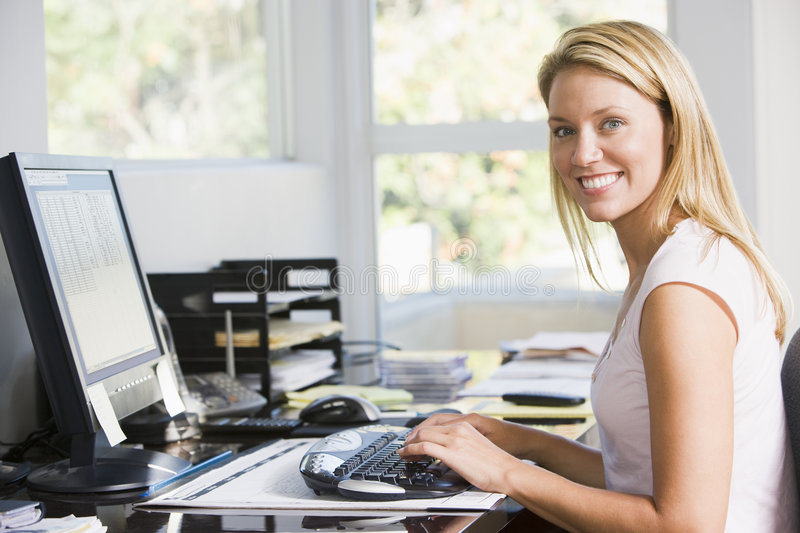 Woman in home office with computer smiling royalty free stock photo