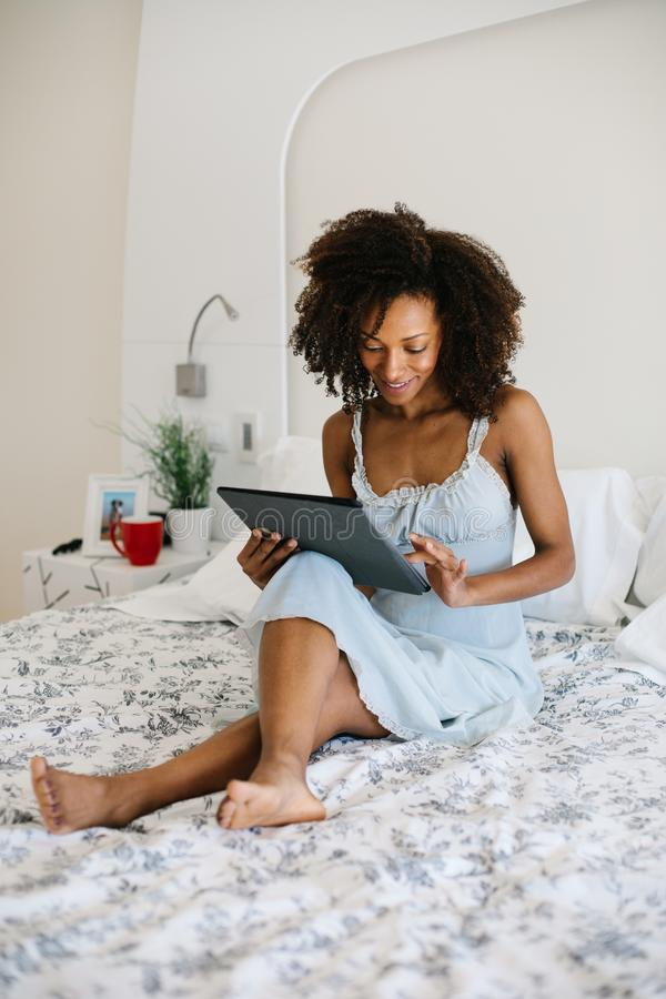 Woman at home reading on digital tablet royalty free stock photography