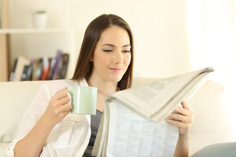 Woman at home reading a newspaper drinking coffee royalty free stock photo