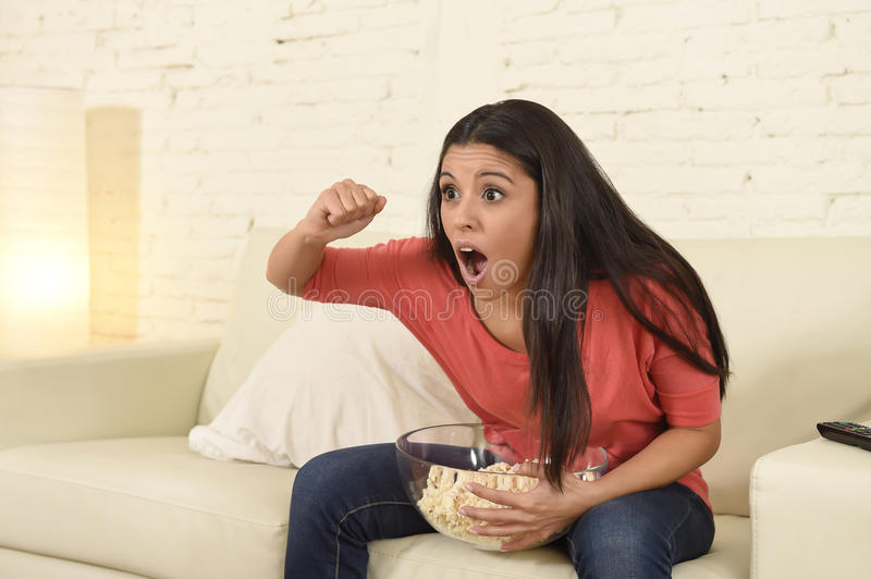 Woman at home sofa couch watching excited tv football sport celebrating victory. Young happy attractive woman alone at home sofa couch watching excited stock photography