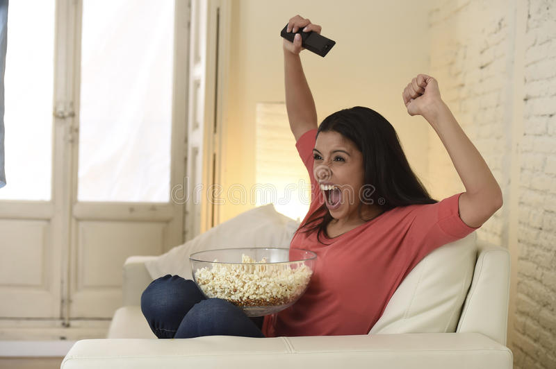 Woman at home sofa couch watching excited tv football sport celebrating victory. Young happy attractive woman alone at home sofa couch watching excited royalty free stock photo