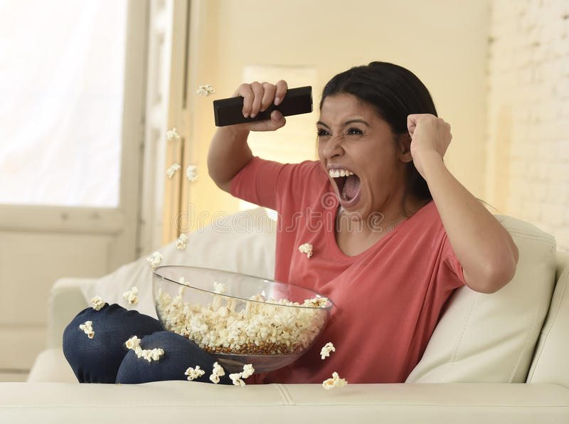 Woman at home sofa couch watching excited tv football sport celebrating victory. Young happy attractive woman alone at home sofa couch watching excited stock photo
