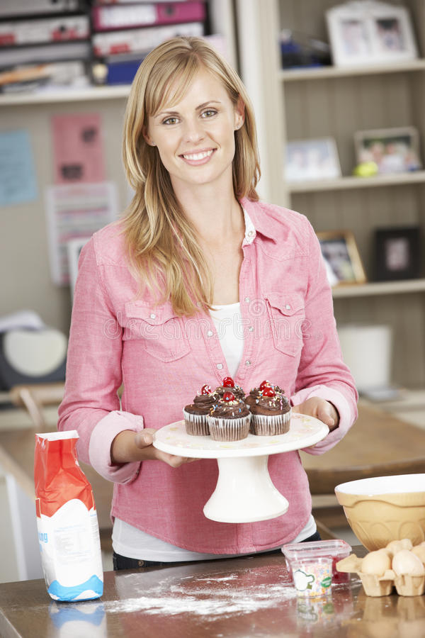 Woman With Homemade Cupcakes In Kitchen stock photos