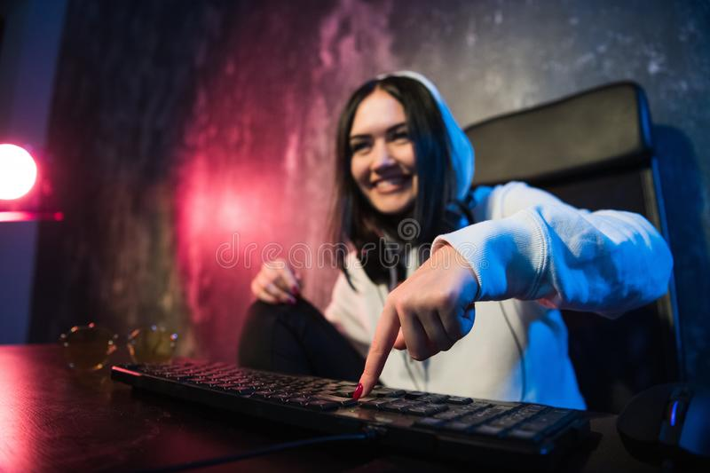 Woman in the hood sitting and working at laptop as hacker. Running malware program on computer in the internet with. Malevolent smile on her face stock image