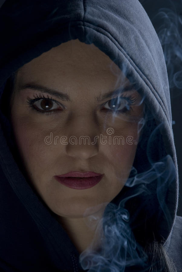 Woman with hood and smoke in darkness. Portrait of woman with hood and smoke in darkness,check also royalty free stock image