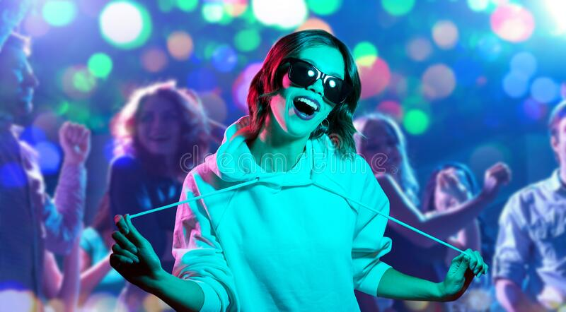 Woman in hoodie and sunglasses at nightclub royalty free stock photography