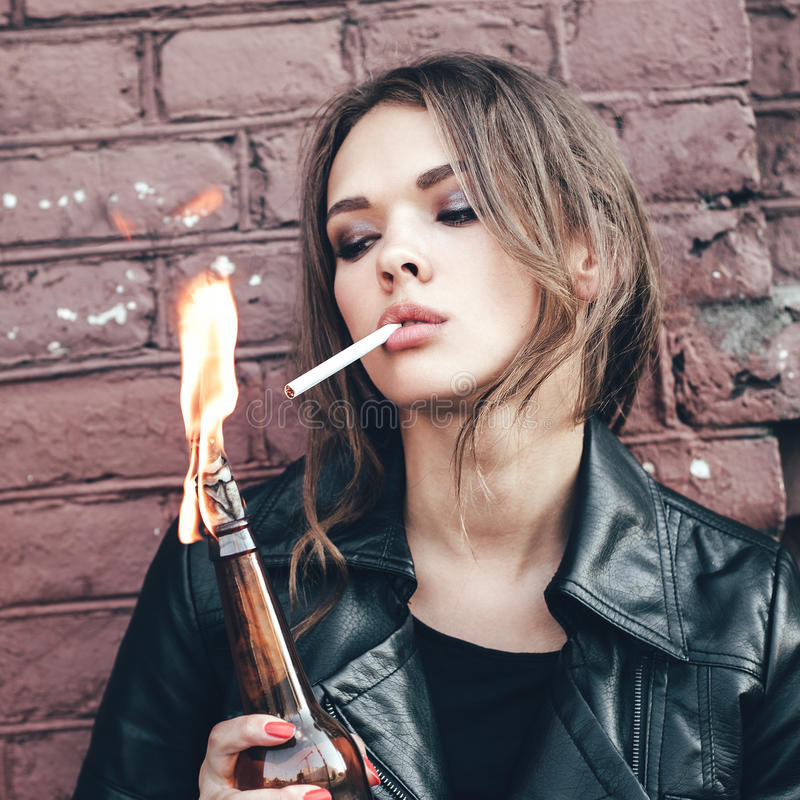 Woman hooligan lighting up a cigarette from Molotov cocktail bomb in her hand stock photography