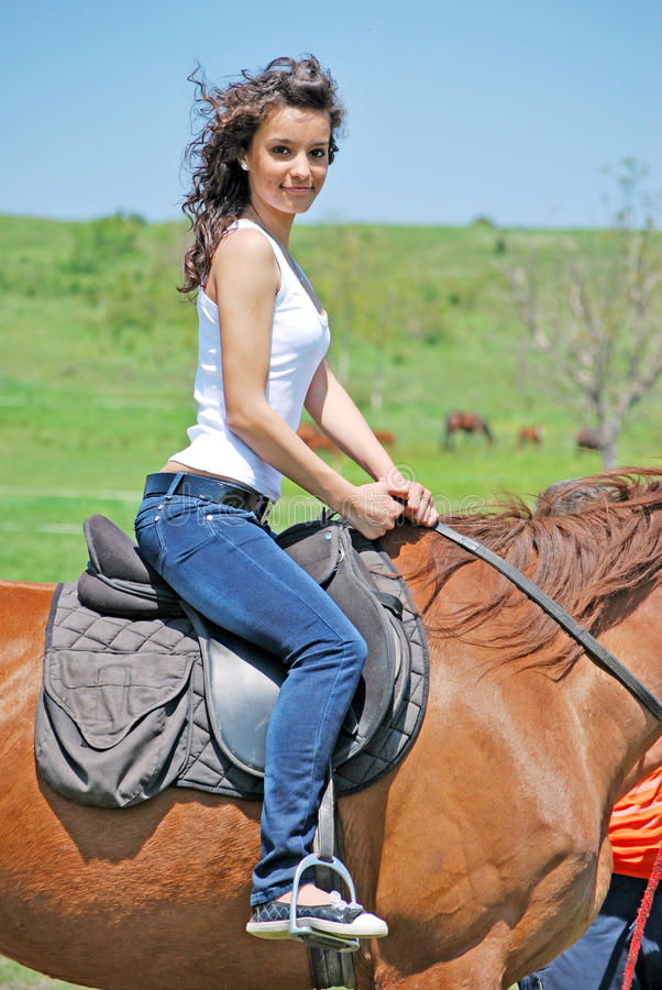 Woman and horse. Young and attractive woman riding brown horse royalty free stock image