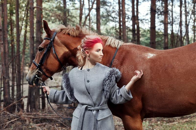 Woman on a horse in the fall. Creative bright pink makeup on the girl face, hair coloring. Portrait of a girl with a horse. Horseb. Ack riding in the autumn stock images