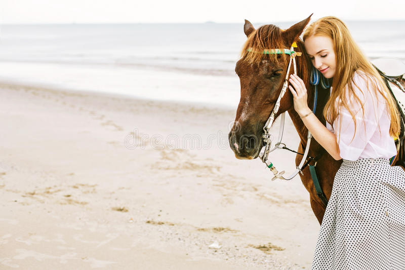 Woman and horse near sea stock photography