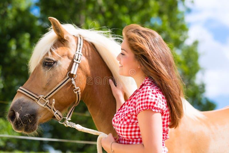 Woman with horse on pony farm royalty free stock photo