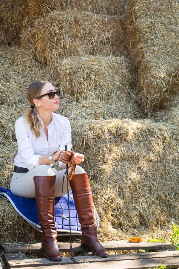 Woman in a horse riding costume resting in the hayloft royalty free stock images