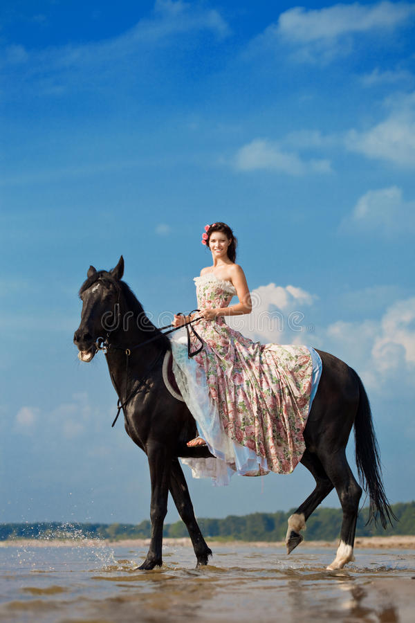 Woman on a horse by the sea royalty free stock photos