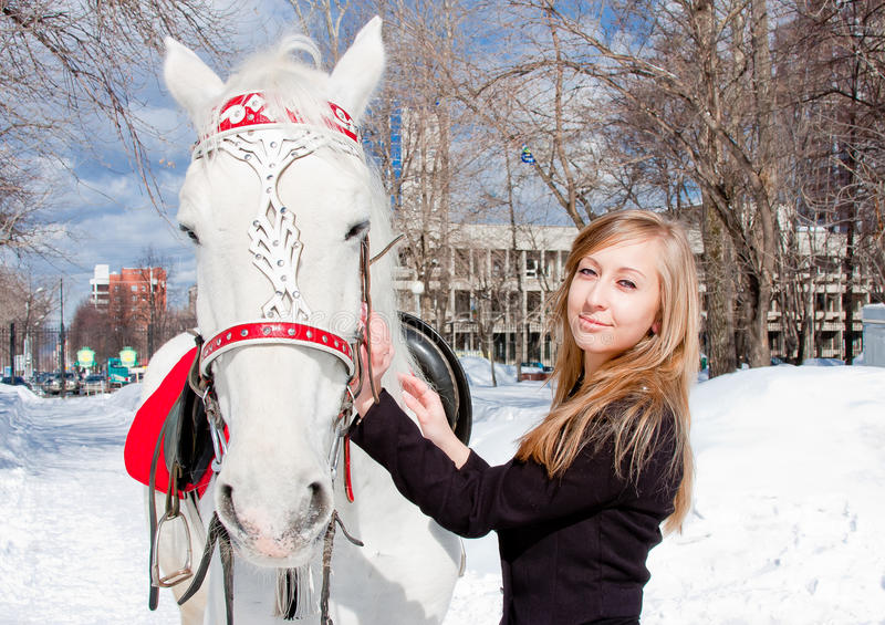 Woman with a horse in a winter park