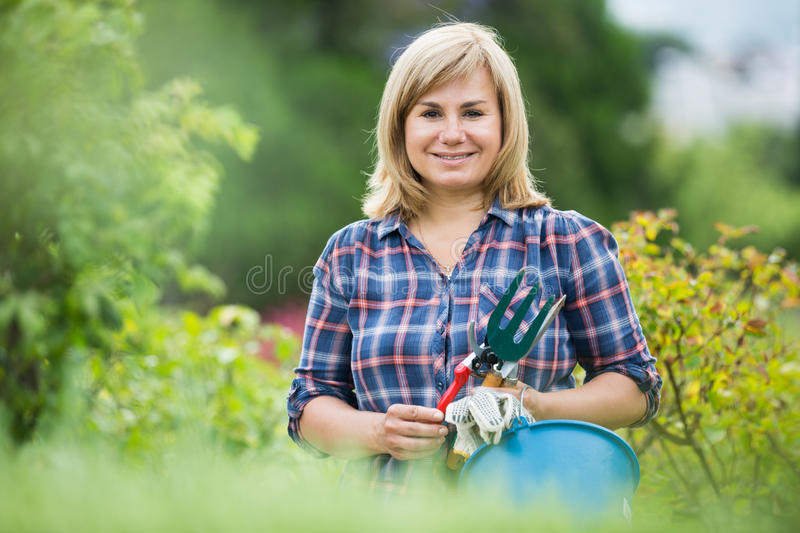 Woman horticultural tools. Portrait of cheerful mature woman with gardening tools standing outdoors royalty free stock photos
