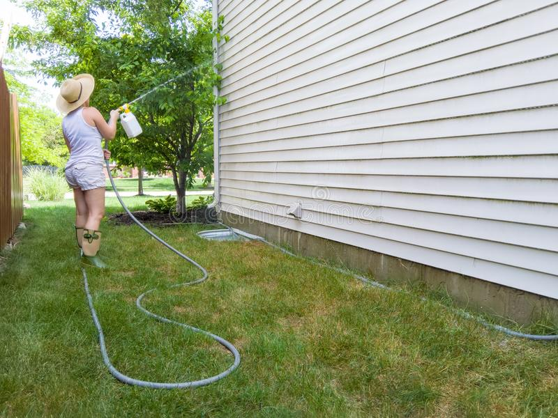 Woman hosing down the sides of her house royalty free stock photos