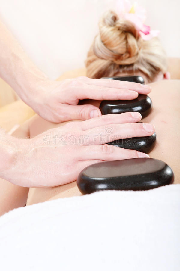 Woman with hot stones in spa. Center royalty free stock image