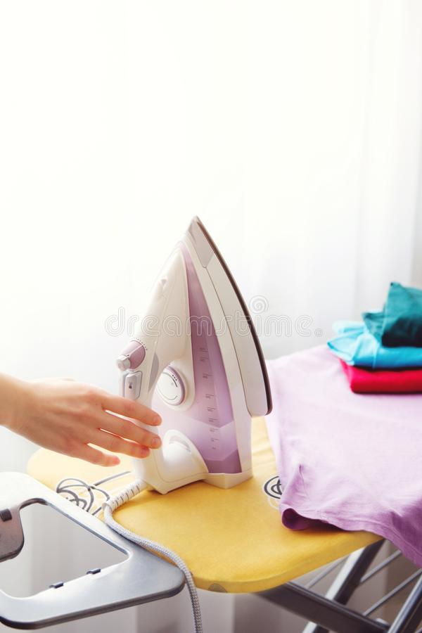 The woman the housewife irons clothes at home. On the Ironing Board iron and purple t-shirt, as well as other things of different stock photography