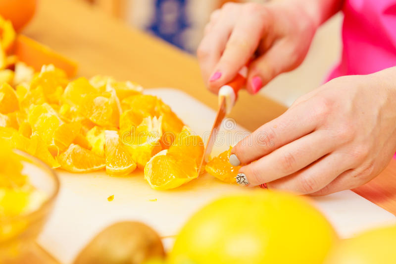 Woman housewife in kitchen cutting orange fruits. Woman young housewife in kitchen at home slicing fresh orange fruits on cutting board for salad or juicing stock photos