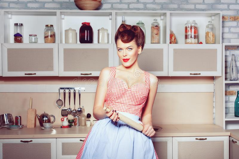 Woman housewife in the kitchen with a rolling pin stock images