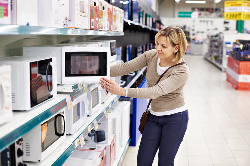 Woman housewife shopping for microwave oven stock photos