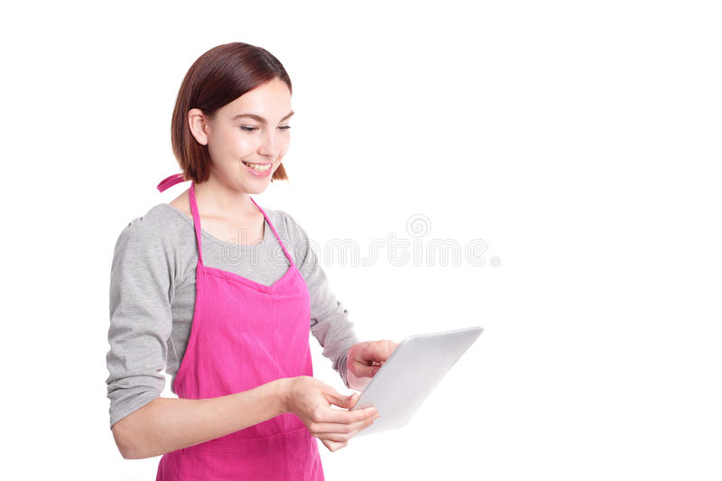Woman housewife with tablet pc. Young woman housewife mother wearing kitchen apron using digital tablet pc, isolated on white background, caucasian stock image