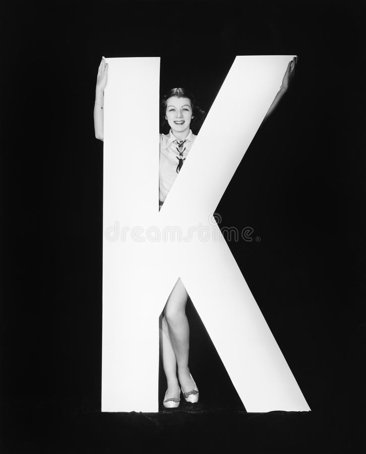 Woman with huge letter K stock photos