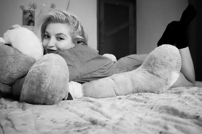 Woman Hugging Bear Lying on Bed stock images