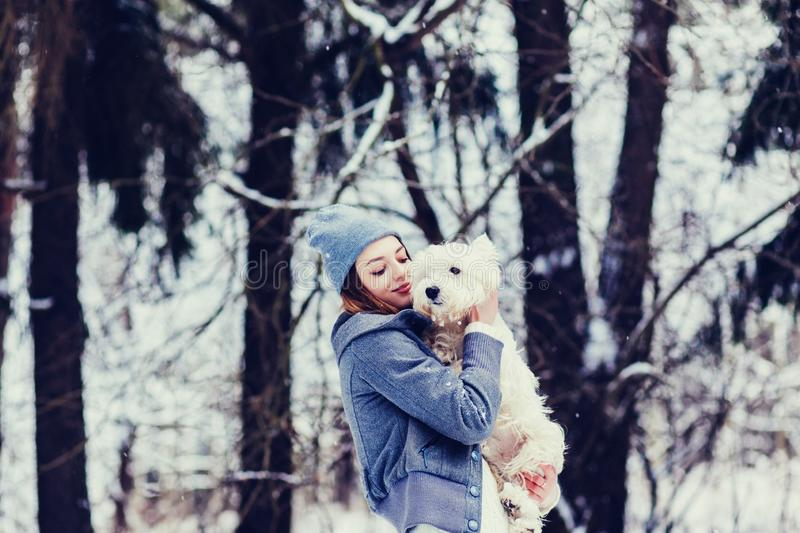 Woman hugging a dog. Wonderful woman hugging a dog in a winter park stock images